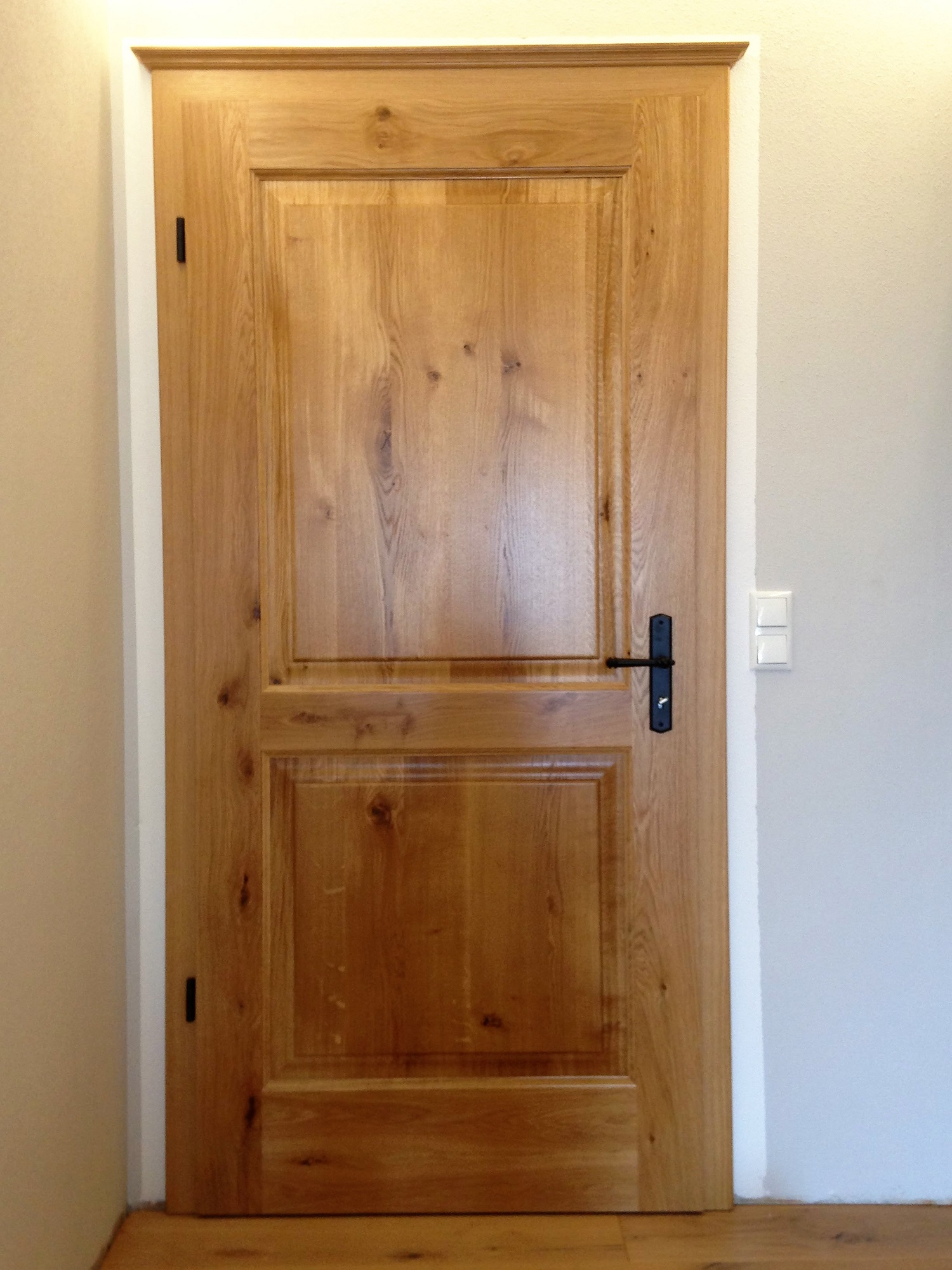 Zimmertür in massiver Asteiche mit Füllung und schwarzen Drücker und Bändern