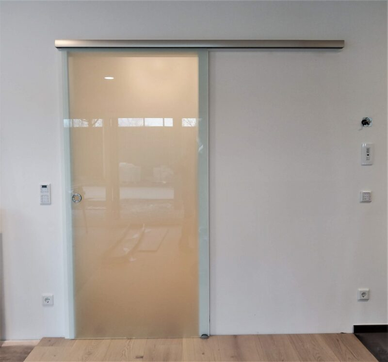 Ganzglas Schiebetüre vor der Wand mit Edelstahlfarbiger Schiene und DuoSoftstop