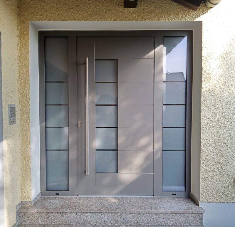 Aluminium Haustüre grau mit Edelstahl-Intarsien und 2 Seitenelementen
